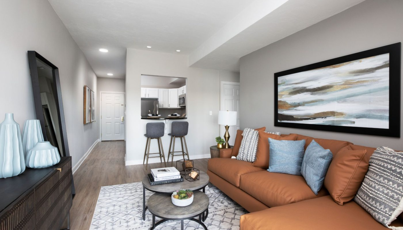 living area with sofa, coffee table, credenza and view of kitchen at j highlands luxury apartments in hudson ma