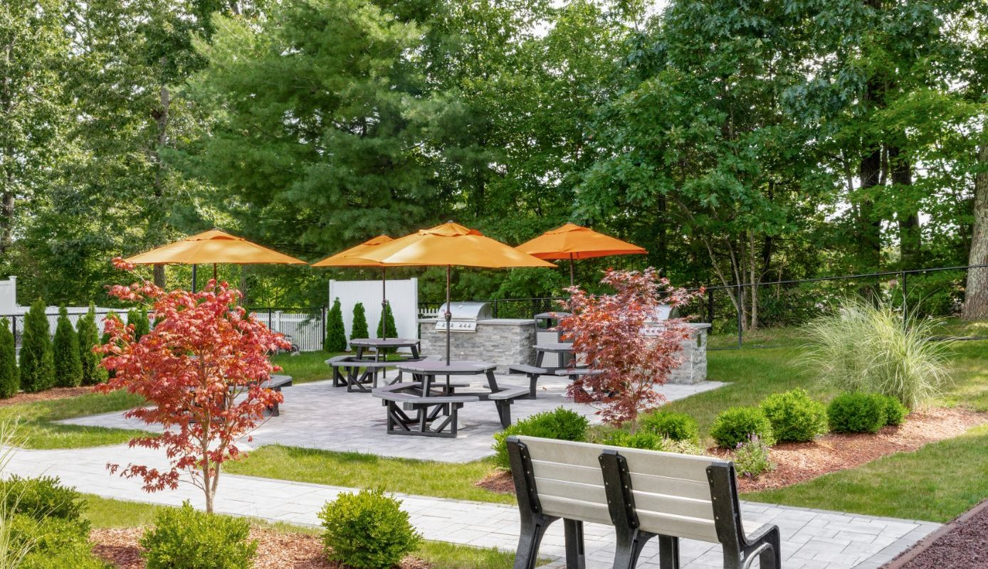 picnic area with tables, chairs, umbrellas and grilling stations at j highlands at hudson apartments