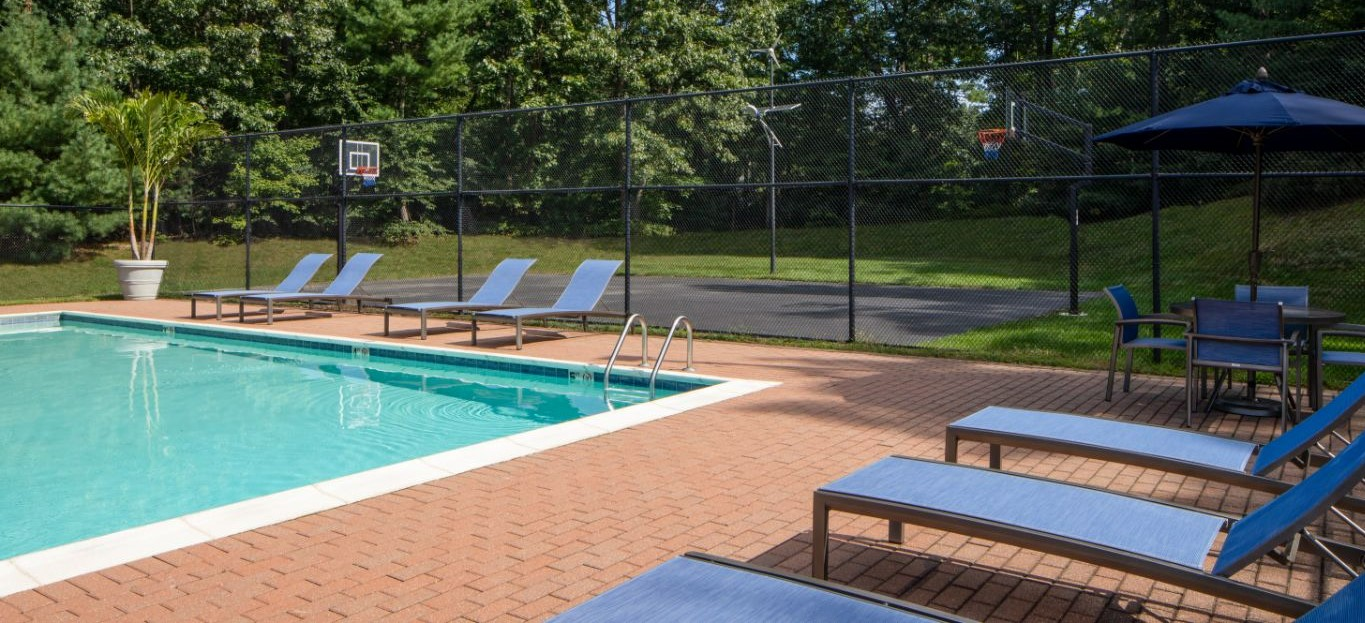 swimming pool, chaise lounge chairs and view of sports court at j highlands at hudson apartments