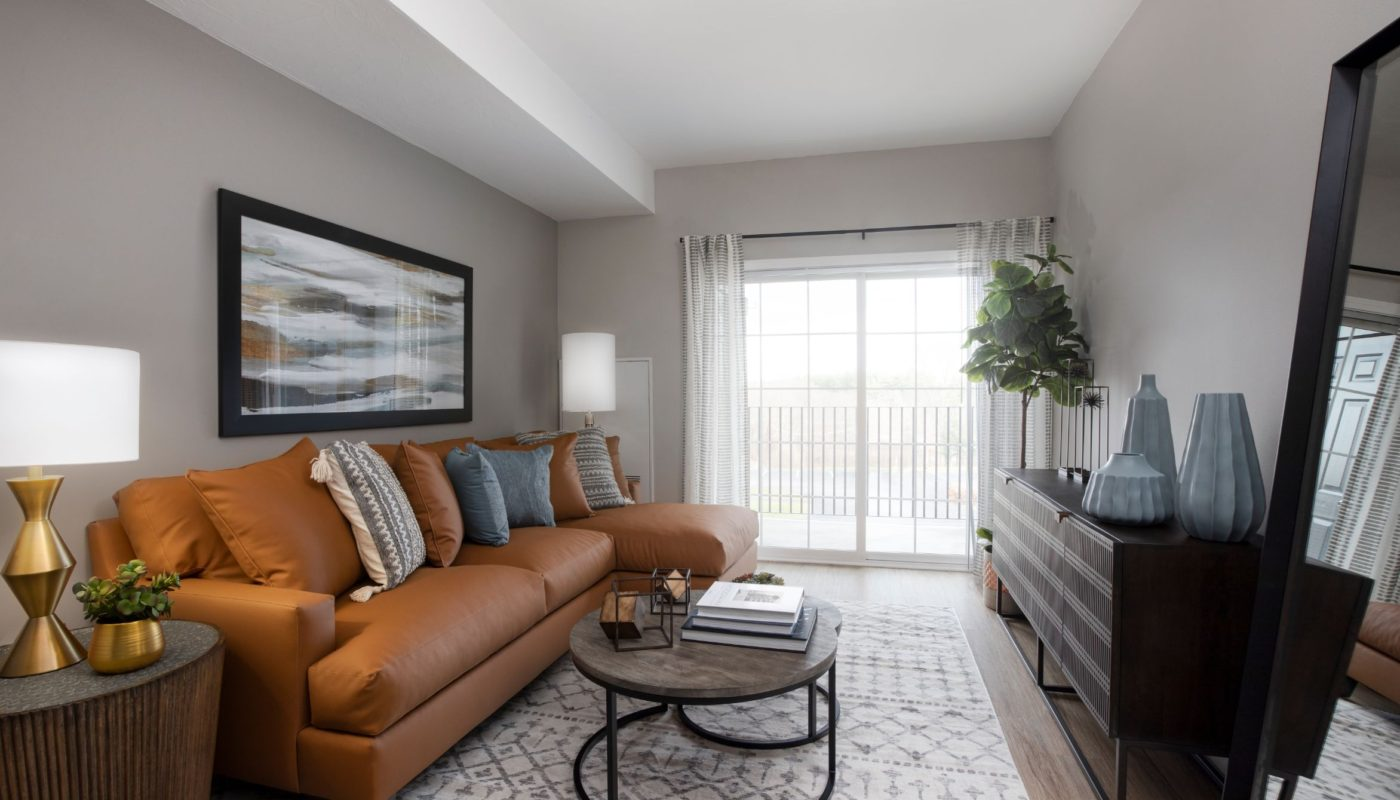 Living area with sofa, coffee table, artwork, and view of balcony at a hudson luxury apartment