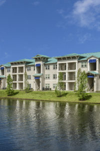 exterior view of pond and 3 story apartment building sea isle luxury apartments orlando