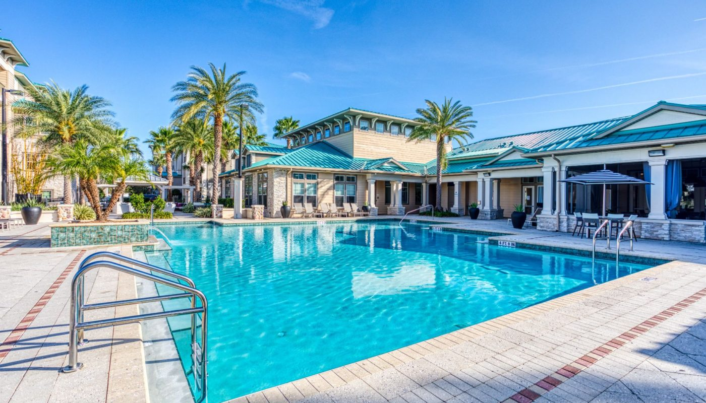 swimming pool with lounge chairs, social seating, umbrellas and a view of the club house at sea isle luxury orlando apartments