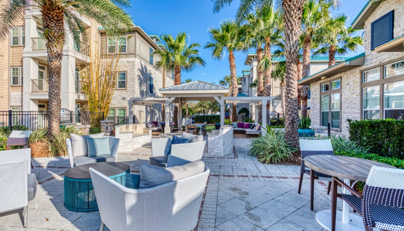 outdoor courtyard with palm trees, social seating, pergola and view of the apartment balconies at sea isle luxury orlando apartments