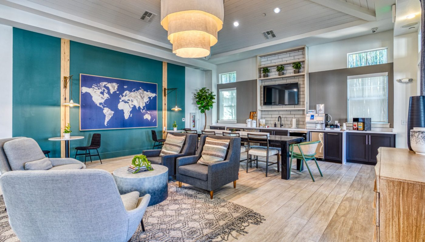 club room with social seating, flat screen tv, wall art and demonstration kitchen at sea isle orlando luxury apartments