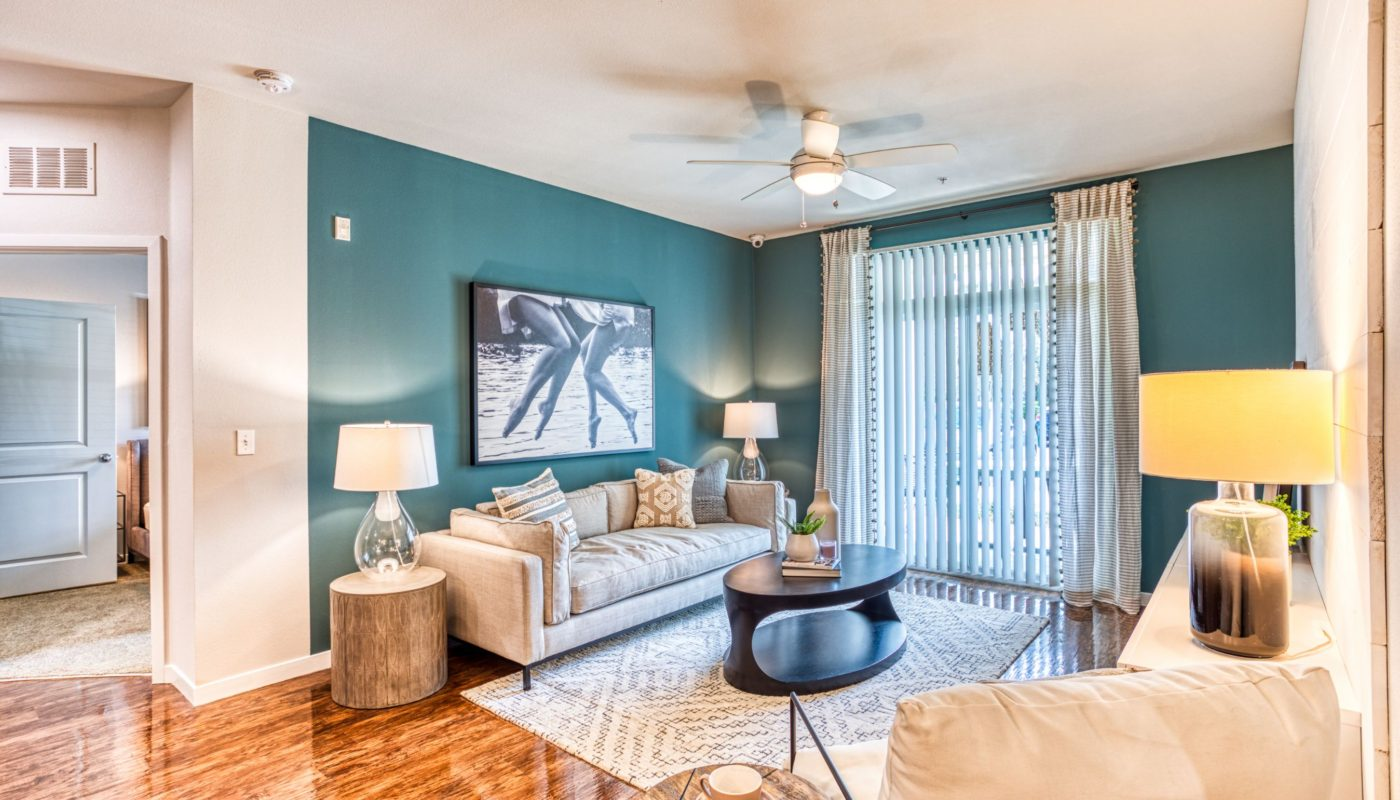 living area with couch, coffee table, end table, decorative lighting, large window, ceiling fan and modern artwork at sea isle luxury apartments