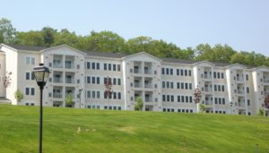 exterior of 4 story apartment building, wooded area and lush lawn at j highlands at hudson luxury ma apartment exterior