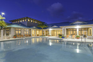 resort style pool, lounge chairs and view of clubhouse in the evening at sea isle apartments in orlando