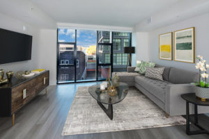 living area with couch, floor to ceiling windows, modern wall art, coffee table, and console with tv at j linea high rise apartments