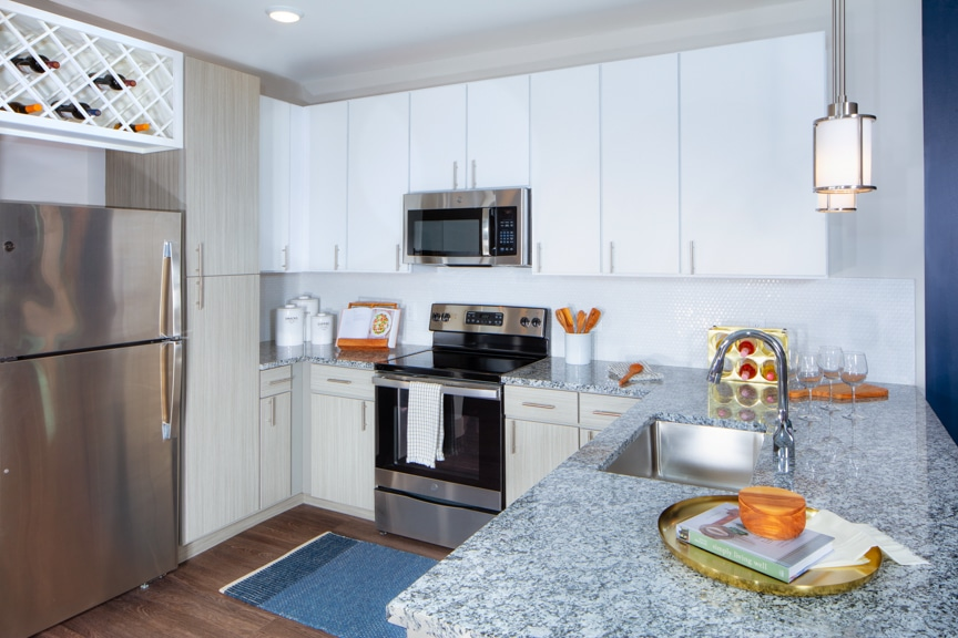 kitchen with stainless steel appliances, granite counters, breakfast bar and wine rack at atelier