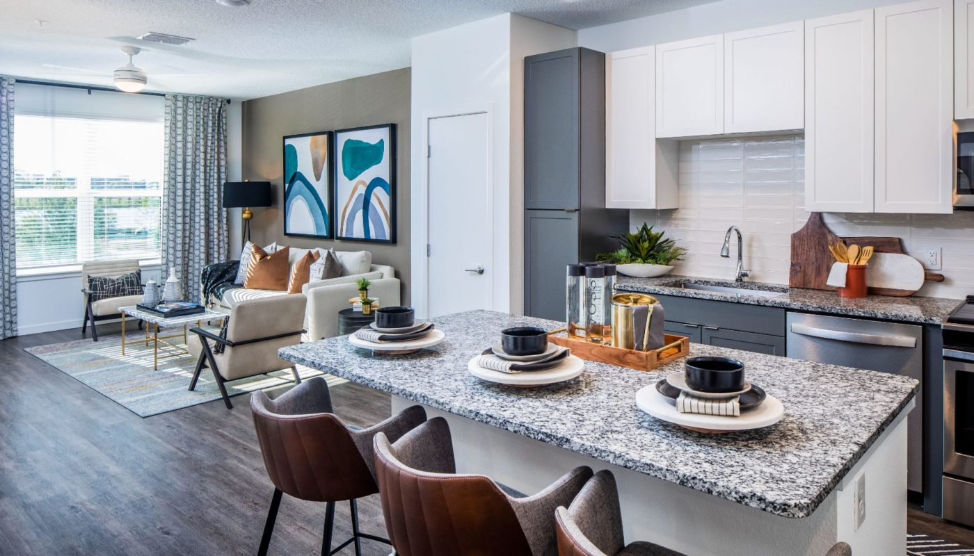 kitchen with island, stainless steel appliances, plank flooring and view of living area at jefferson sand lake in orlando