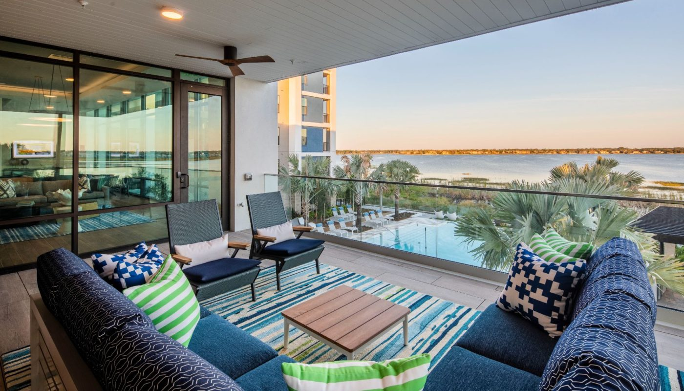 covered outdoor lounge with social seating, cocktail tables, and view of pool at jefferson sand lake in orlando fl